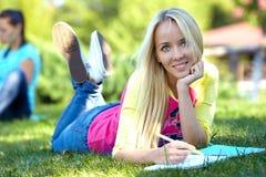 De mooie student ligt op groen gazon en leert stock fotografie