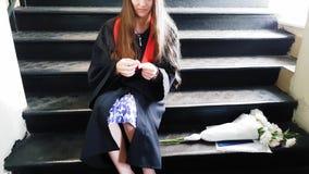 De mooie studenten gediplomeerde meester bindt haar been met een pleister vast terwijl het zitten op metaalstappen bij de univers stock footage