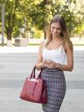De mooie telefoon van de bedrijfsmeisjesholding en een beurs Royalty-vrije Stock Foto