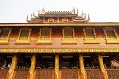 De mooie Thaise stijl houten bouw met veelvoudige vensters met gouden kaders in een Boeddhistische tempel in Thailand stock foto