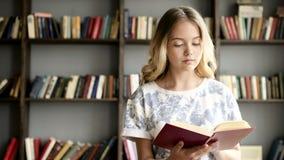 De mooie tiener leest een literatuur op school stock videobeelden