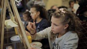 De mooie tienerzitting bij de schildersezel schildert een beeld in een kunstacademie Professionele kunstacademie voor kinderen stock footage