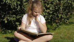 De mooie tienerzitting op een gras in de zomerpark en leest boek Langzame Motie stock video