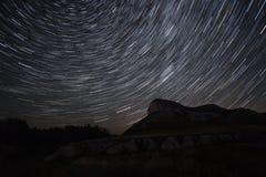 De mooie tijd-tijdspanne van sterslepen over de heuvels Polaire Poolster op het centrum van omwenteling Royalty-vrije Stock Fotografie