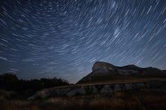 De mooie tijd-tijdspanne van sterslepen over de heuvels Poolster op het centrum van omwenteling Royalty-vrije Stock Afbeeldingen