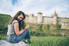 De mooie toerist zit op rots voor oud kasteel en eet aplle Royalty-vrije Stock Foto's