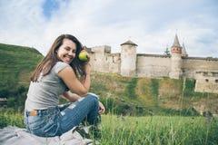 De mooie toerist zit op rots voor oud kasteel en eet aplle Stock Afbeelding