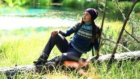 De mooie toeristenvrouw met rugzak in warme sweater en hoed zit op een gevallen boom door bergmeer Front View stock videobeelden