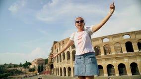 De mooie toeristenvrouw stelt dichtbij Roman colosseum Langzame Motie stock videobeelden