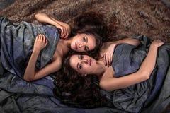 De mooie tweelingen jonge vrouwen met natuurlijke samenstelling en haarstijl die met hun krullend haar liggen omringen hen Stock Fotografie