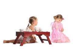 De mooie tweelingenzusters hebben geïsoleerden thee Royalty-vrije Stock Afbeeldingen