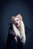De mooie vampier van het blondemeisje met bloed is op de mond royalty-vrije stock afbeelding