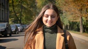De mooie verrukkelijke Kaukasische vrouw loopt naar camera en glimlacht met gelukkig Ce-ontspannen gezicht, beweging stock footage