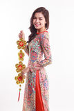 De mooie Vietnamese vrouw die indrukao dai dragen die gelukkig verfraait voorwerp houden Royalty-vrije Stock Foto