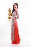 De mooie Vietnamese vrouw die indrukao dai dragen die gelukkig verfraait voorwerp houden Stock Foto