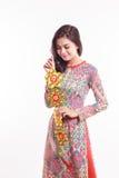 De mooie Vietnamese vrouw die indrukao dai dragen die gelukkig verfraait voorwerp houden Royalty-vrije Stock Foto's