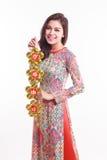De mooie Vietnamese vrouw die indrukao dai dragen die gelukkig verfraait voorwerp houden Royalty-vrije Stock Fotografie