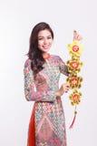 De mooie Vietnamese vrouw die indrukao dai dragen die gelukkig verfraait voorwerp houden Royalty-vrije Stock Afbeeldingen
