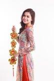 De mooie Vietnamese vrouw die indrukao dai dragen die gelukkig verfraait voorwerp houden Stock Afbeelding