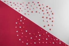 De mooie vlakte legt patroon van harten met exemplaar-ruimte op grijze en rode achtergrond voor de Dag van Valentine ` s Royalty-vrije Stock Afbeelding