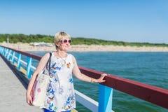 De mooie volwassen vrouw in zon-bescherming glazen bevindt zich in brug royalty-vrije stock foto