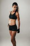 De mooie vrouw in atletische borrels staart bij camera Royalty-vrije Stock Afbeeldingen