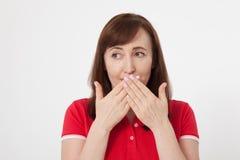 De mooie vrouw behandelt haar mond met haar handen voor geïsoleerd stil Rode t-shirt en het houden van een geheim royalty-vrije stock fotografie
