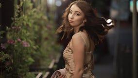 De mooie vrouw bekijkt terug camera en gaat in nachtstad weg, langzame motie stock video