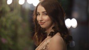 De mooie vrouw bekijkt terug camera en gaat in nachtstad weg, langzame motie stock videobeelden