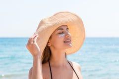 De mooie vrouw beschermt haar huid op gezicht met sunblock bij het strand stock foto