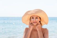 De mooie vrouw beschermt haar huid op gezicht met sunblock bij het strand stock fotografie
