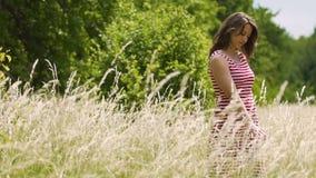 De mooie vrouw bevindt zich op gebied wat betreft lange gewassen, strelend tarwe met hand stock video