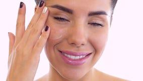 De mooie vrouw bevochtigt gezicht met room stock videobeelden