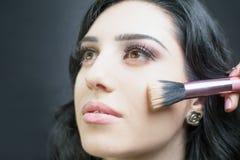 De mooie vrouw bij schoonheidssalon ontvangt make-up Stock Foto
