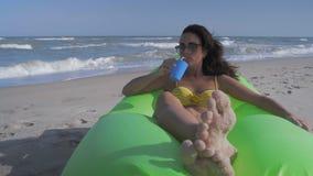 De mooie Vrouw in Bikini ontspant op het Overzeese het Liggen Strand op de Groene Opblaasbare Opgevulde Pool en drinkt Cocktail stock video