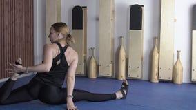 De mooie vrouw is binnen op yogaklasse in moderne studio stock footage