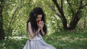 De mooie vrouw in blauwe kleding geniet van een geur van verse rode appel stock video