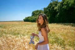 De mooie vrouw, de bruid met blauwe ogen en het bruine haar lopen door graangebied op een zonnige de zomer` s dag, het lachen stock foto's