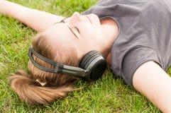 De mooie vrouw in close-up die op gras liggen en luistert muziek royalty-vrije stock foto's