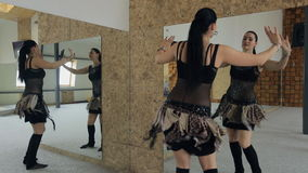 De mooie vrouw danst buikdans in studio met vele spiegels Mening van rug stock videobeelden