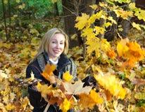 De mooie vrouw in de herfstpark werpt op esdoornbladeren Stock Foto's