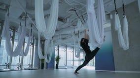 De mooie vrouw die been het uitrekken doen zich zet één been in hangmat voor yoga en een andere binnen op de vloer in studio stock footage