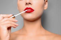De mooie vrouw die rood toepassen polijst op lippen tegen grijze achtergrond stock afbeelding
