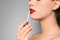 De mooie vrouw die rood toepassen polijst op lippen tegen grijze achtergrond, close-up stock foto