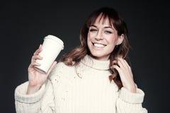 De mooie vrouw die sweater dragen houdt document beschikbare koffiekop Drinkende koffie, het glimlachen en het lachen stock afbeelding