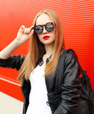 De mooie vrouw die van de portretmanier een jasje, de zonnebril en de zak van het rots zwart leer over rood dragen Royalty-vrije Stock Foto