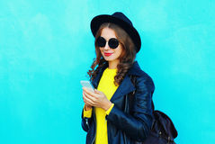 De mooie vrouw die van het manierportret smartphone gebruiken die kleren van een de zwarte rotsstijl over kleurrijk blauw dragen Stock Afbeelding