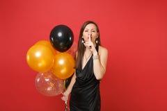 De mooie vrouw die in zwarte kleding stilte zeggen stil is met vinger op lippen, shhh gebaar het vieren, houdend luchtballons stock fotografie