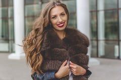 De mooie vrouw draagt luxe donkere bontjas Stock Afbeelding