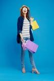 De mooie vrouw in een hoed en met glazen houdt heel wat pakketten op een blauwe achtergrond, het winkelen, shopaholic klant, Stock Afbeeldingen